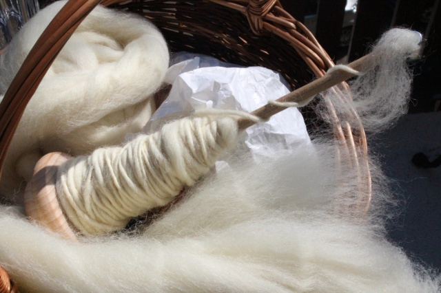Ein Korb, in dem sich eine Papiertüte, ein Bausch Fasern aus cremeweißer Eiderwolle und eine Handspindel befindet, die zur Hälfte mit Eiderwolle vollgesponnen ist.
