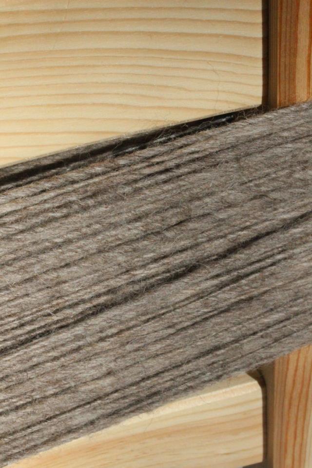 frisch versponnene Wollfasern in dunklen Sandfarben um die Lehne eines Kieferstuhls gewickelt