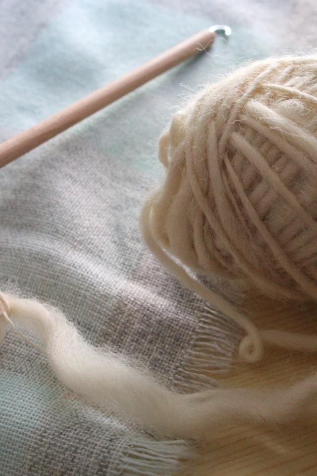 Spindelstab und Knäuel aus weißer selbstgesponnener Wolle auf einer pastelligen Tischdecke in weichem Licht.