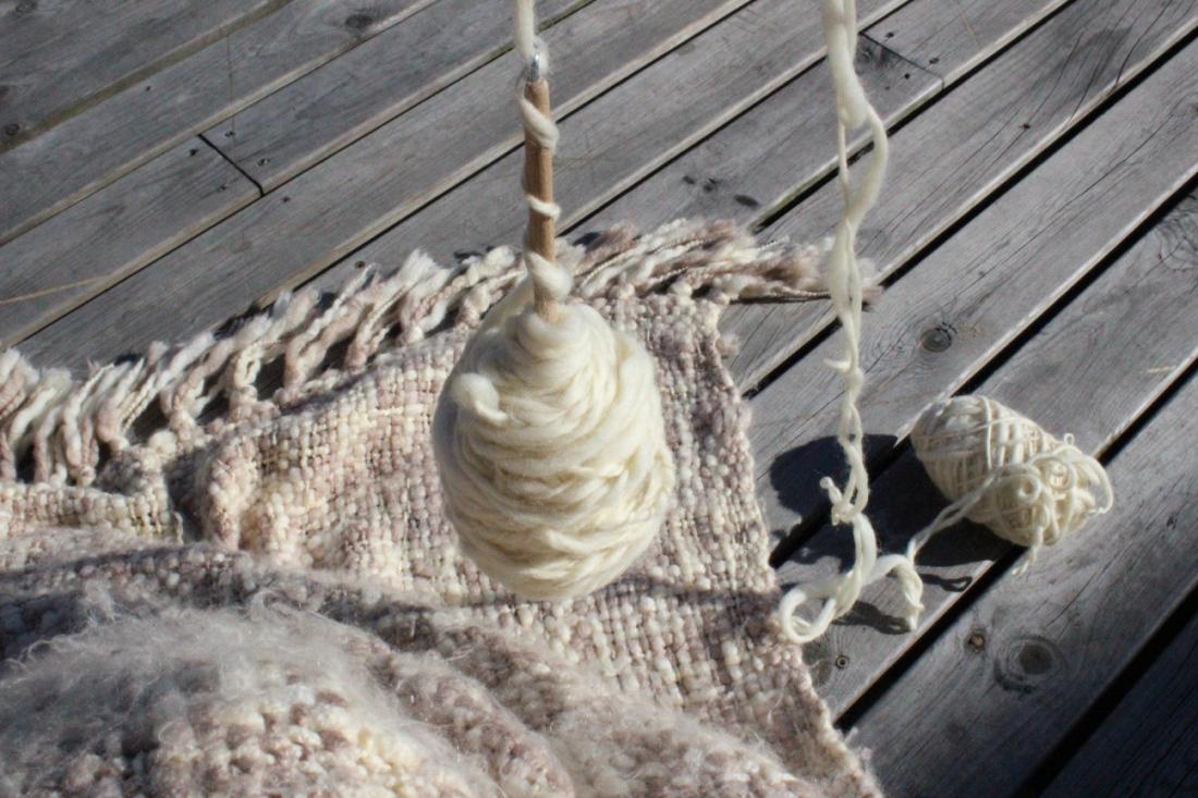 Blick vom Sitzen auf die Decke auf meinem Schoß, einer dick mit verzwirntem Garn behongenen Spindel und zwei Fäden gesponnener Eiderwolle, die aus zwei Enden eines Knäuels kommen, das auf Holzterassenboden rumliegt.