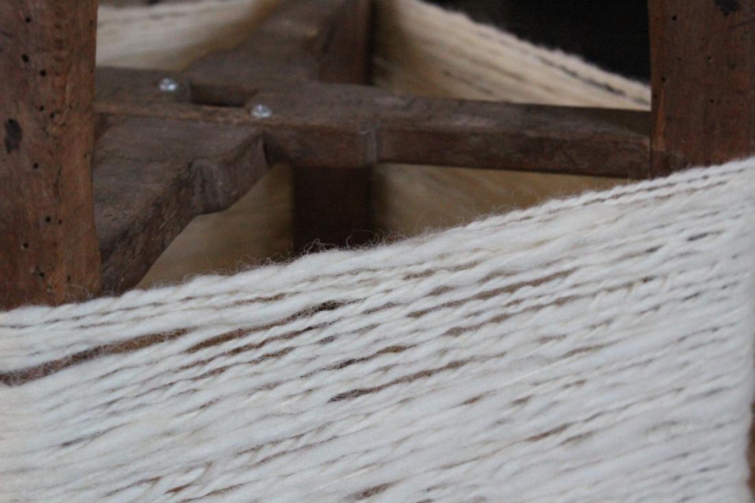 Nahaufnahme eines Strangs verzwirnter Eiderwolle, die auf den Beinen eines umgedrehten Holzhockers so rundherum aufgespannt wurde.