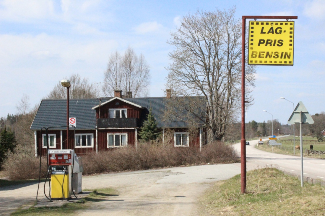 """Verlassene Selbstbedienungstankstelle vor einem schwedenroten Familienhaus. Zwei freistehende Zapfsäulen ohne Dach, am straßenrand ein Schild auf dem auf Schwedisch """"Niedrigpreisbenzin"""" steht."""