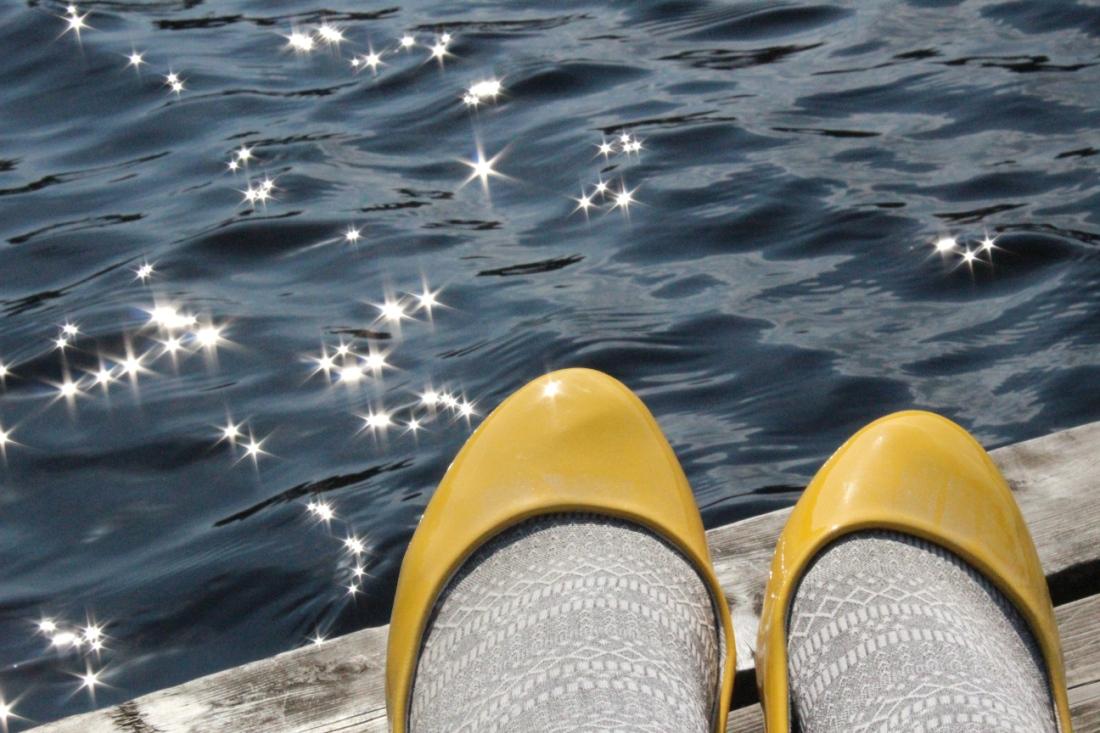 Steg am Wasser,. darauf die Spitzen von gelben Lackschuhen, in denen hellgraue Strumpfhosenbeine stecken, die Sonne reflektiert Sterne auf das dunkle Wasser.