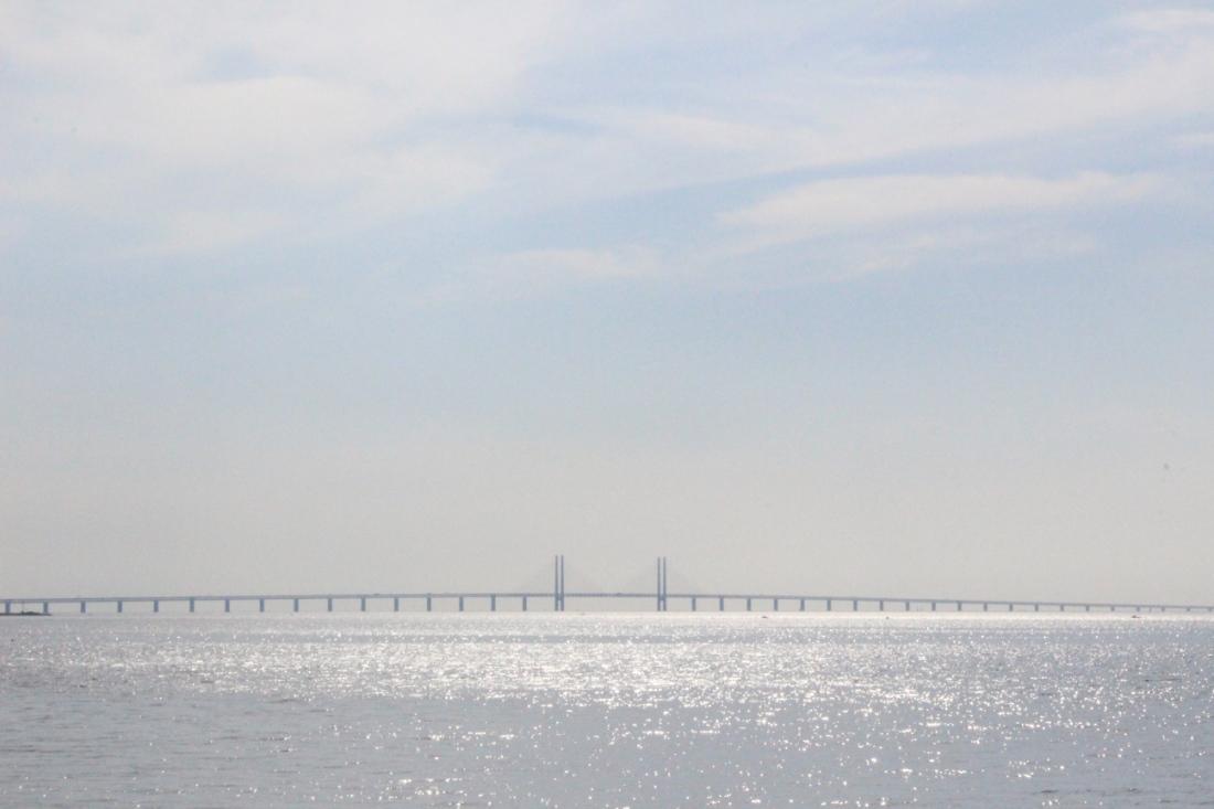 Die Brücke von Kopenhagen nach Malmö weit hinten im Meer, verschwommen in Lichtschimmer.