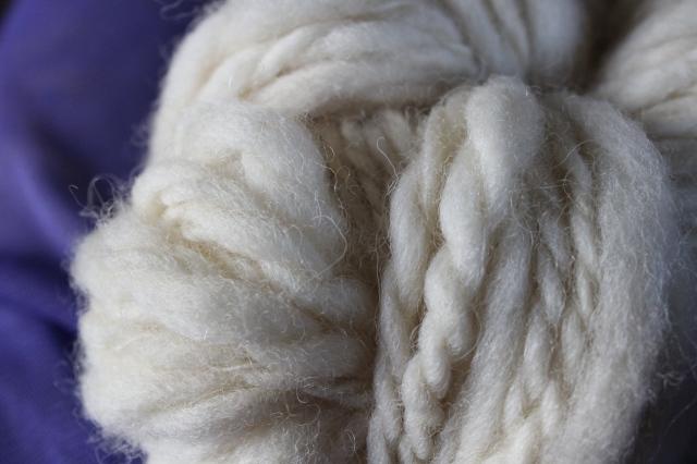 Fertiges Eiderwollgarn als Knäuel in Nahaufnahme, liegt auf einem Hintergrund aus lila Tüll.