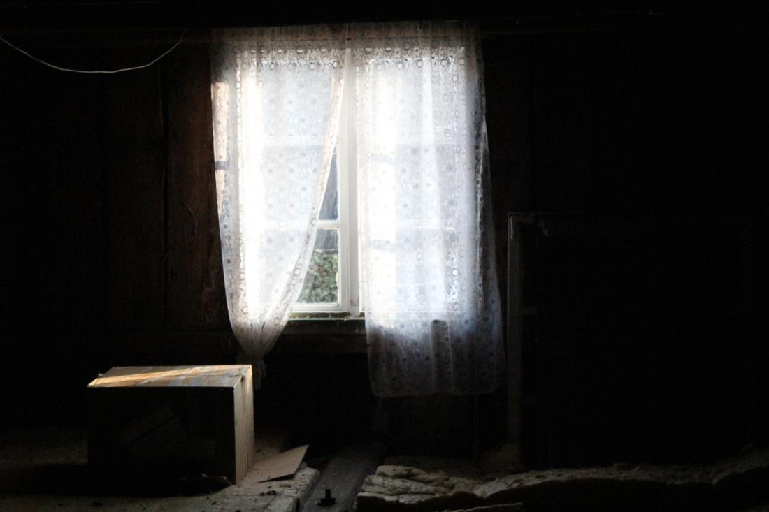Dachbodenfenster, das wenig Licht auf den dunklen Boden wirft. Da ein paar Isoliermatten auf dem Boden, dortt eine Kiste. Und Gardinen am Fenster.