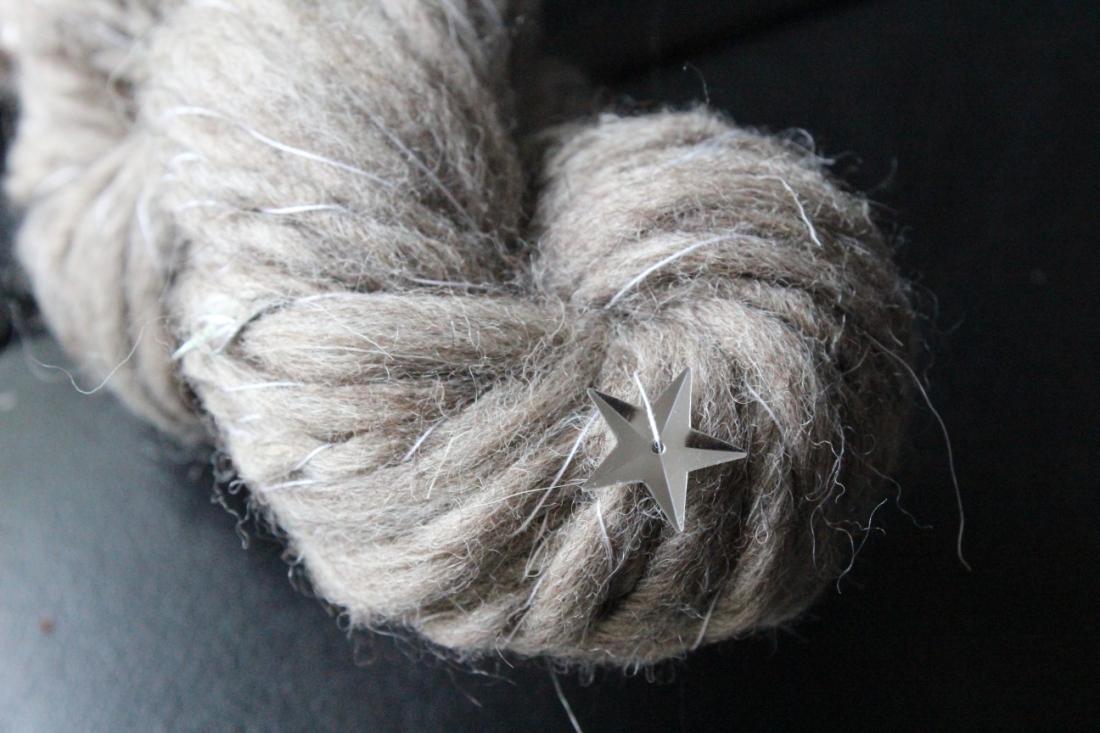 Hellgraues Knäuel Wolle mit metallischen Plastiksternchen darin