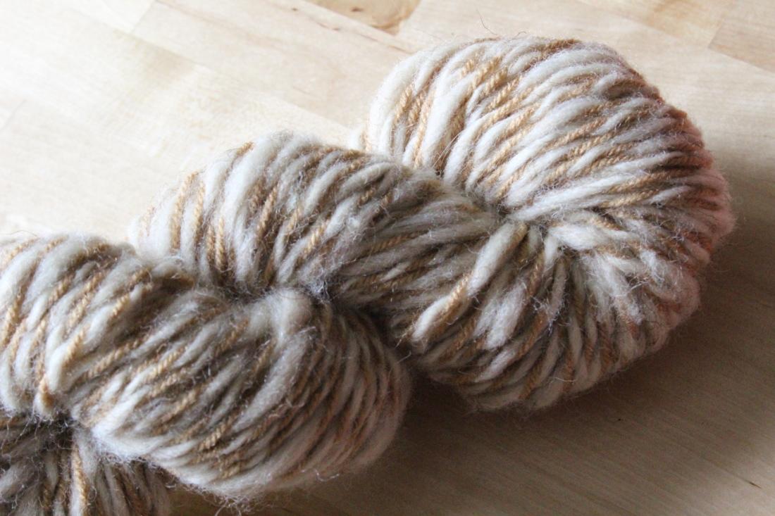 Garnbündel hellbraune Wolle, das auf einem Brikenholztisch liegt