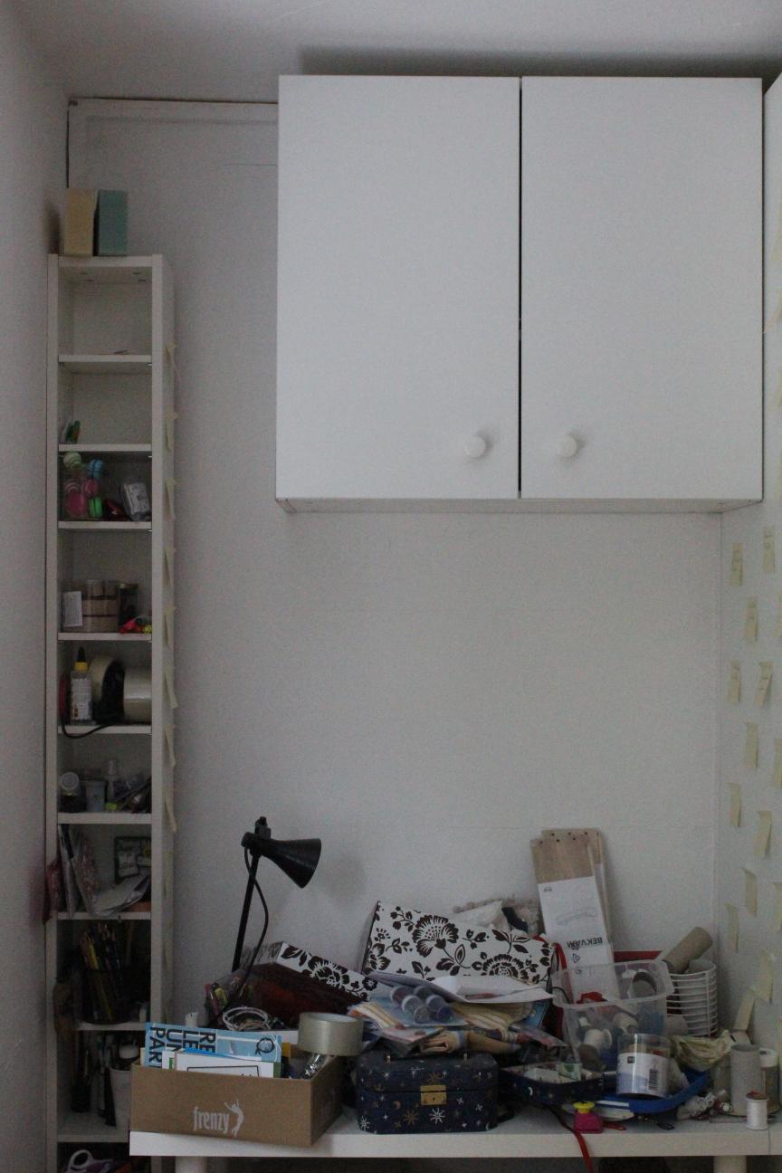 Ein weißer Schreibtisch, vollgestapelt mit Zeug und Kram und Kisten, Bastelsachen, eine Lampe, Postkarten und Glitzertuben. Links davon ein weißes Ikea-CD-Regal, eion bisschen aufgeräumter, darin Kleber und Scheren und Einmachgläser mit Krimskrams. Oben drüber ein weißer Schrank an der Wand, beide Türen verschlossen, endlich was, das ordentlich aussieht.