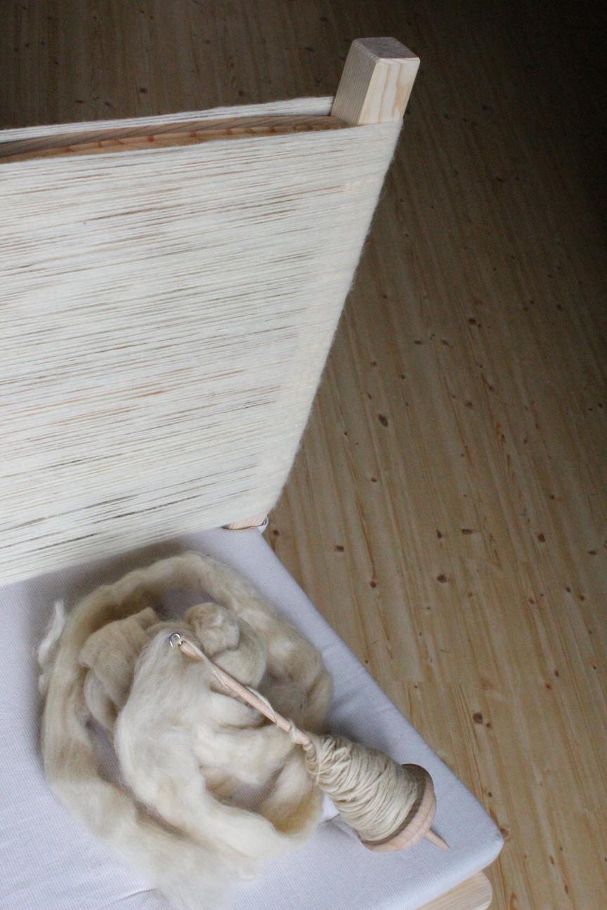 Halber Ausschnitt von einem Stuhl, dessen Lehne komplett mit feinem weißem Garn aufgewickelt ist. Auf dem Sitz liegt eine Handspindel mit etwas gelberen Fasern, die schon angesponnen sind.