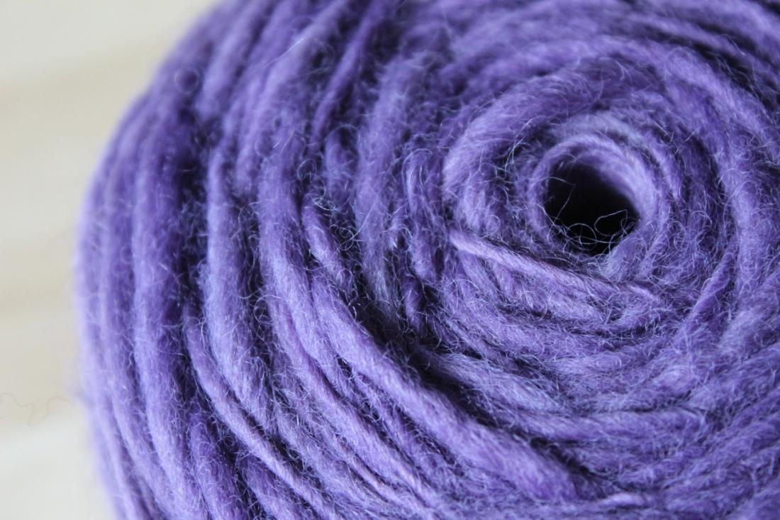 Knäuel lavendellila Garn, kreisrund aufgewickelt.