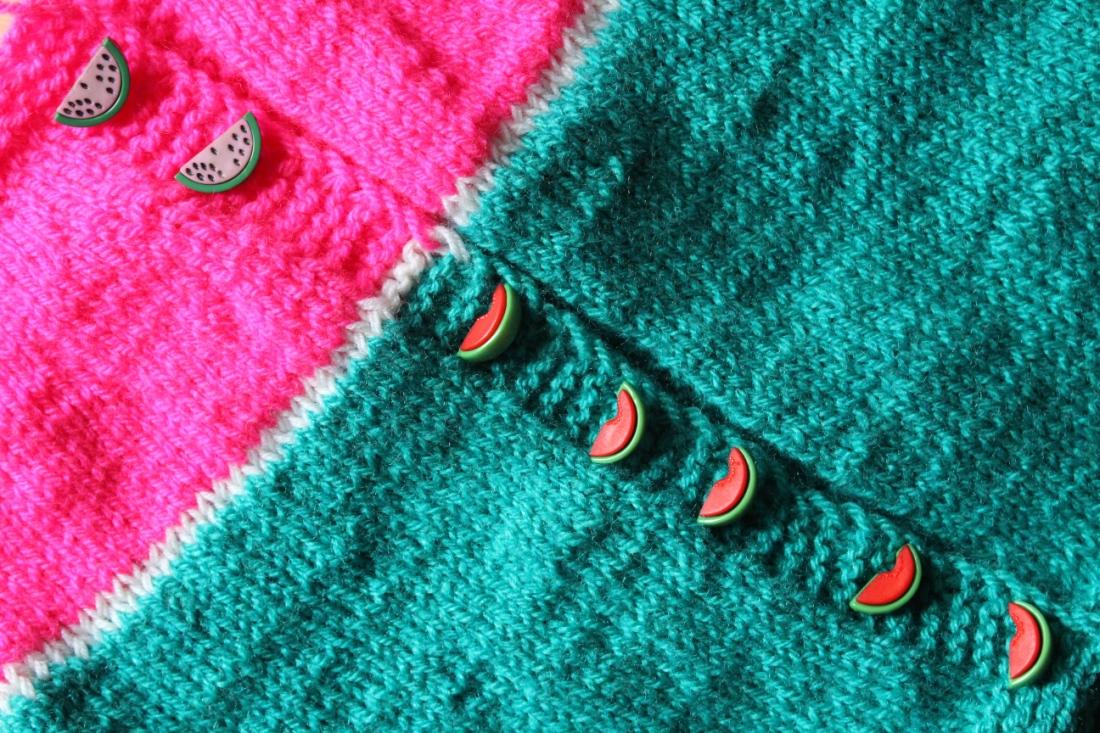 Knopfleiste einer Strickjacke, die zu einem drittel pink, zu zwei dritteln grün ist. Auf der Knopfleiste liegen wassermelonenförmige Knöpfe, auf der grünen Wolle mit rotem Fruchtfleisch, auf der pinken Wolle mit rosa Fruchtfleisch.