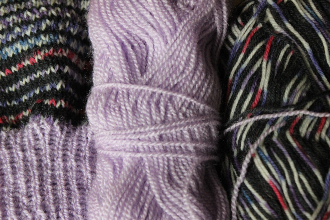 Zwei Garnknäuel, eines helllila, das andere schwarz mit weiß und lilarotblau gemischt liegen neben einem Strickstück, in dem beide Knäuel zu gleichen Teilen verstrickt sind.