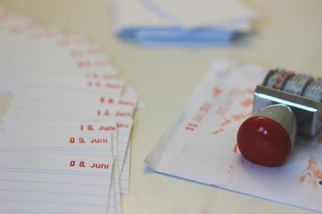 Viele Karteikarten, auf denen je ein Datum oben rechts hingestempelt ist. Im Vordergrund der 8. Juni.Rechts daneben ein Datumsstempel auf einem verschmierten Papierumschlag. hinten noch ein Stapel Karteikarten.