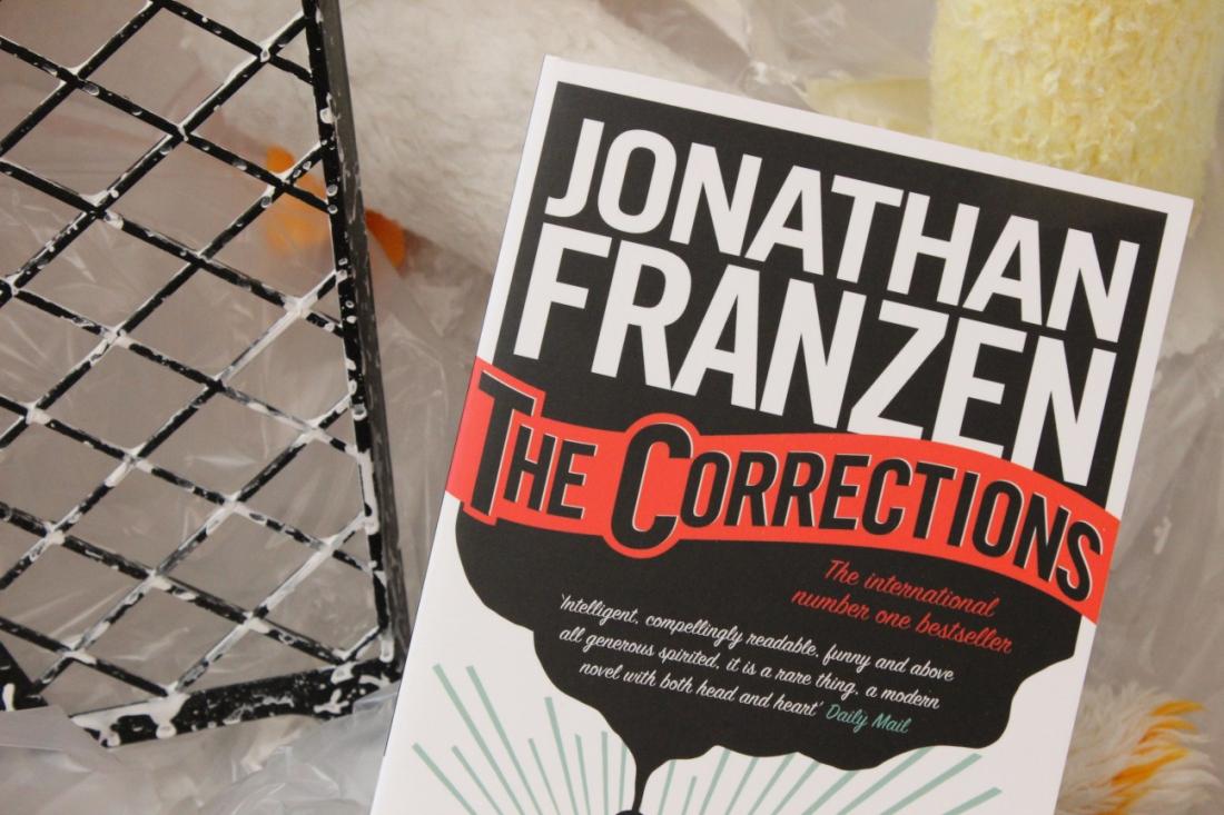 """Das Buch """"The Corrections"""" von Jonathan Franazen in einer Malereikiste mit Abrollgitter und Farbrollen im Hintergrund."""