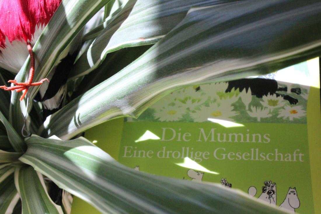 """Das Buch """"Die Mumins, eine drolliige Gesellschaft"""" von Tove Jansson hinter ein paar Zimmerpflanzenblättern, auf denen ein Vogel sitzt, von dem man nur das Plastikbeinchen im Licht sieht."""