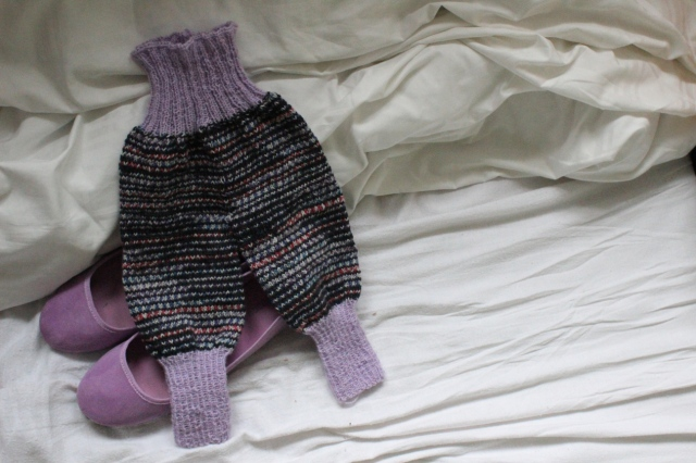 Selbstgestrickte Krembelhose mit lila Fuß- und Bauchteil und dunkelgestreiften Beinen, die auf zwei lila Ballerinas in einem weißbezogenen Bett liegt.