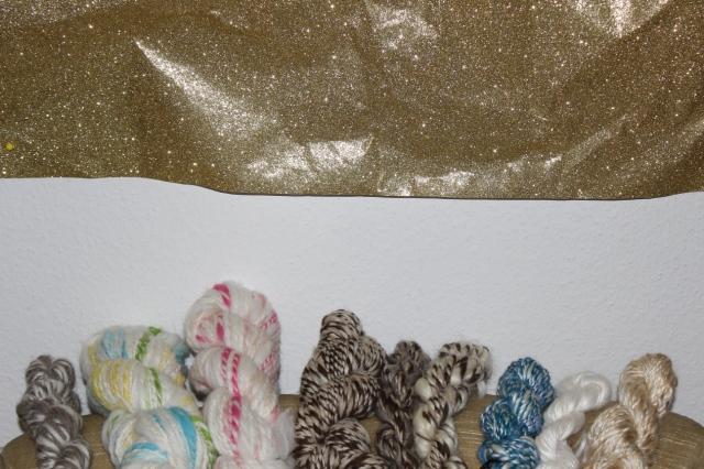 verschiedene handgesponnene Wolle auf einer beigen Sessellehne, darüber an der Wand Goldglitzergeschenkpapier.