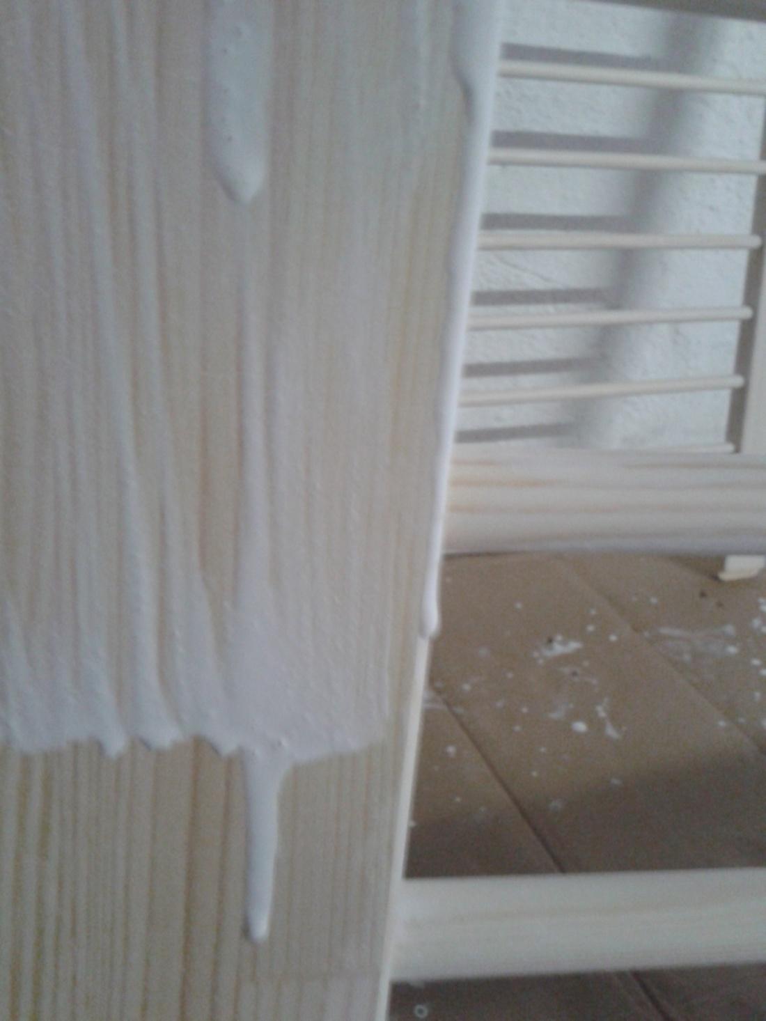 Mit weißer Holzlasur bestichene Holzplatte, von der die Lasur runtertropft, vor einer bereits gestrichenen Sprossenwand.