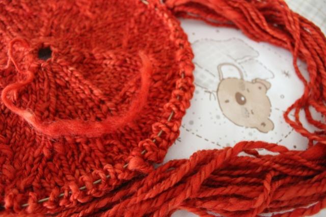 andere angestrickte Babydecke aus dem gleichen Garn. liegt auf einer Wickelauflage, auf der ein schlafendes Bärchen abgebildet ist.