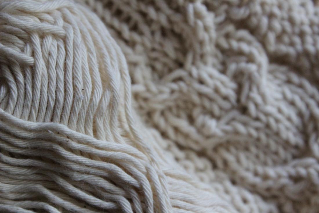 Weißes Baumwollknäuel, etwas unschärfer dahinter mit eben jenem Knäuel gestricktes Eulenmuster