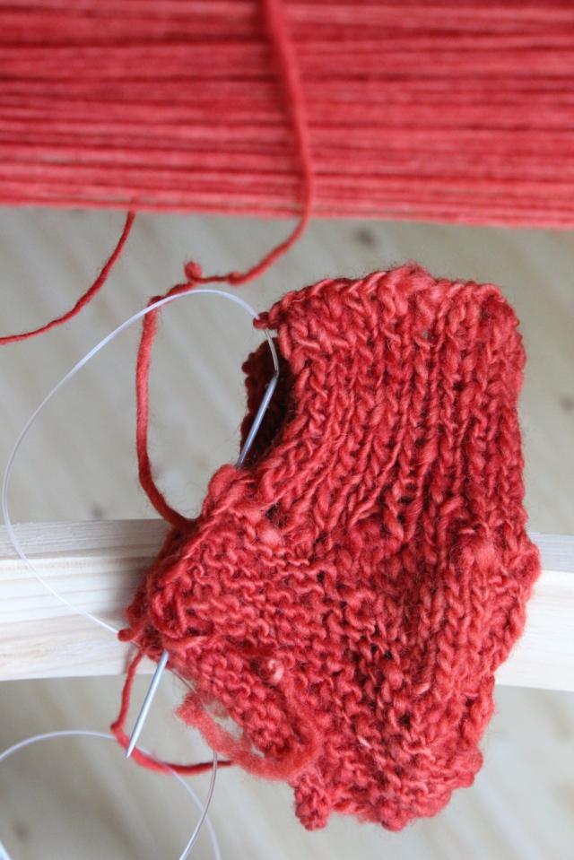 Rotes Strickstück, aus dem mal ein Kinderschuh werden soll, wenn er vernäht ist, irgendwann.