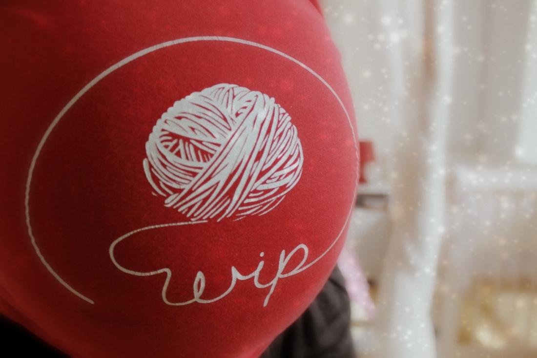 """Bauchfoto, auf dem T-Shirt steht in kugelrunder Bauchhöhe """"wip"""", die Buchstaben schlängeln sich aus einem gezeichneten Wollknäuel."""