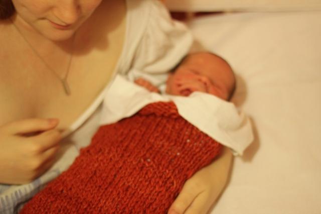 Ein frischgeborenes Baby in einem tiefroten Stricksack, im Arm gehalten von einer weißen Frau, die in einem weiß bezogenen Bett liegt und nur von der Nase bis zur Brust im Bild ist.