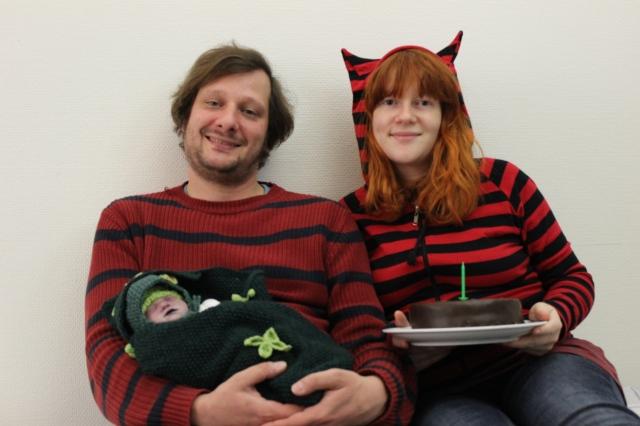 Zwei erwachsene Menschen in gestreiften Pullovern sitzen vor einer weißen Wand und lächeln. Er, links, hält ein in eine grüne Decke gewickeltes Baby, sie hat eine Kaputze mit Öhrchen und hält eine Sachertorte, auf der eine grüne Kerze steckt.