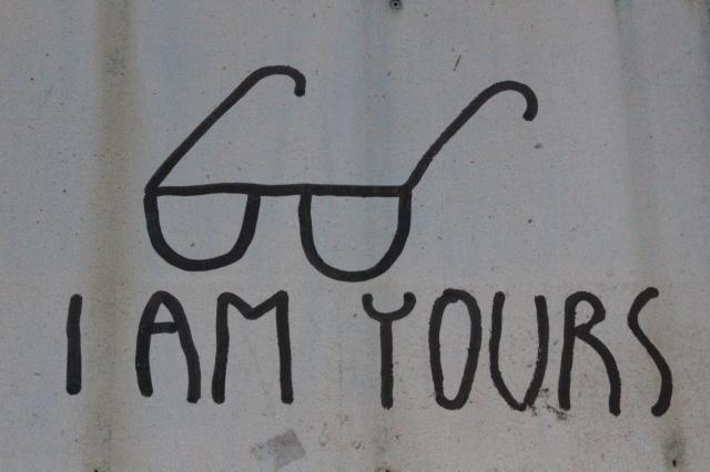 """Foto von Street Art: in Versalien """"I AM YOURS"""", darüber eine simple Lesebrille gemalt, wie mit dickem Edding."""