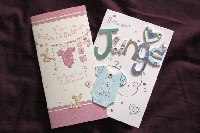 Zwei Glückwunschkarten, auf deren Titelseite in rosa Dekoration Glückwünsche zum Mädchen und in hellblauer Dekoration Glückwünsche zum Jungen stehen.