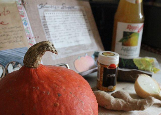 Kürbissuppenzutaten vor dem aufgeschlagenen Buch, nämlich Kürbis (who guessed?), Ingwer, Zwiebel, Curry, Räuchertofu und eine Flasche naturtrüber Apfelsaft.