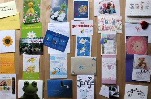 Karten zur Geburt des Kindes, auf dem Tisch, sortiert nach Farben. Links die gelben Karten, dann die grünen, die blauen, die lila-farbenen und die rosanen.