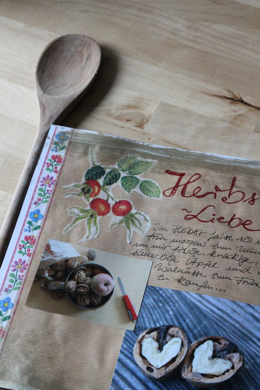 Eine Seite mit Fotos von Äpfeln und Walnüssen mit herzförmigem Nusskern, daneben liegt ein Kochlöffel aus Holz.