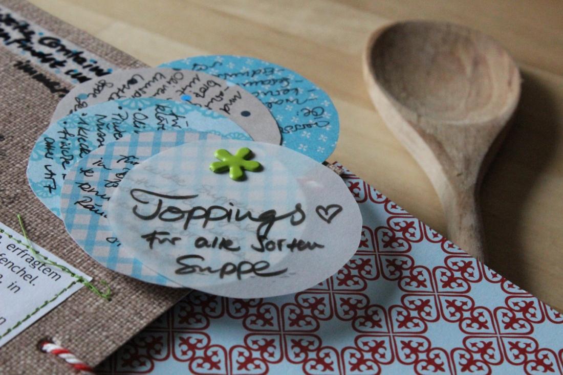 Kreise aus verschiedenem Papier, auf den Toppingmöglichkeiten stehen, so ins Buch gemacht, dass sie sich auffächern lassen.