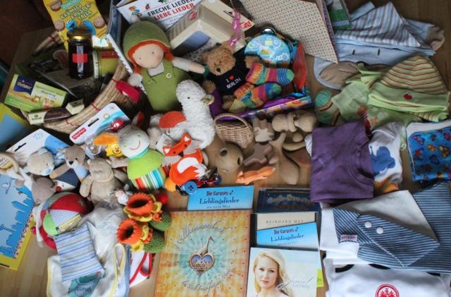 Foto mit fast allen Geschenken zur Geburt des Babys, ausgebreitet auf einem Tisch, Bücher, CDs, Kuscheltiere, Spucktücher, Rasseln, Kleidung, Schuhe, Puppen, Spielfiguren, Essen und mehr.