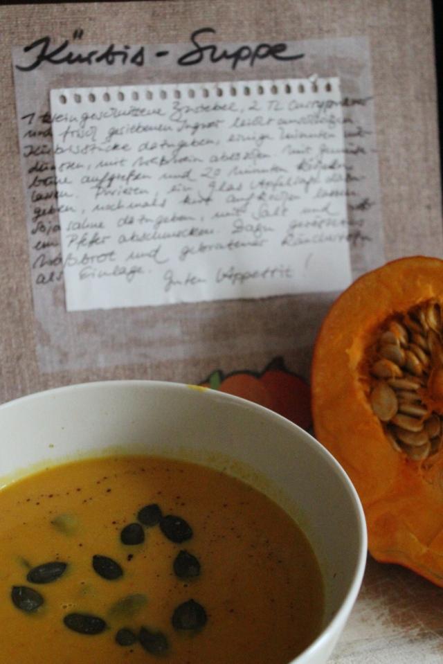 Die fertige Suppe und die übriggebliebene Kürbishälfte vor der aufgeschlagenen Rezeptseite; in der suppe schwimmen Kürbiskerne in Herzformation.