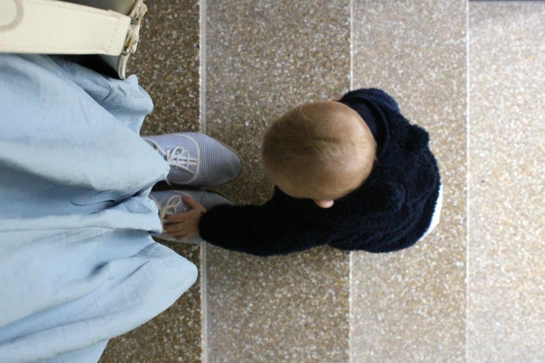 Vier Treppenstufen, von oben draufgeguckt: auf der obersten steht eine erwachsene Person, von ihr sind nur zwei blei-weiß-gestreifte Stoffstchuhe, ein taubenblauer Rock und eine weiße Kunstledertasche zu sehen. Die Person guckt in Richtung trepperunter. Zwei Stufen unter ihr steht ein Baby in einem dunkelblauen Teddyfelljäckchen mit Kapuze. Das Baby ist die Stufen von unten nach oben hochgeklettert und fasst mit der linken Hand den rechten Schuh der erwachsenen Person an.