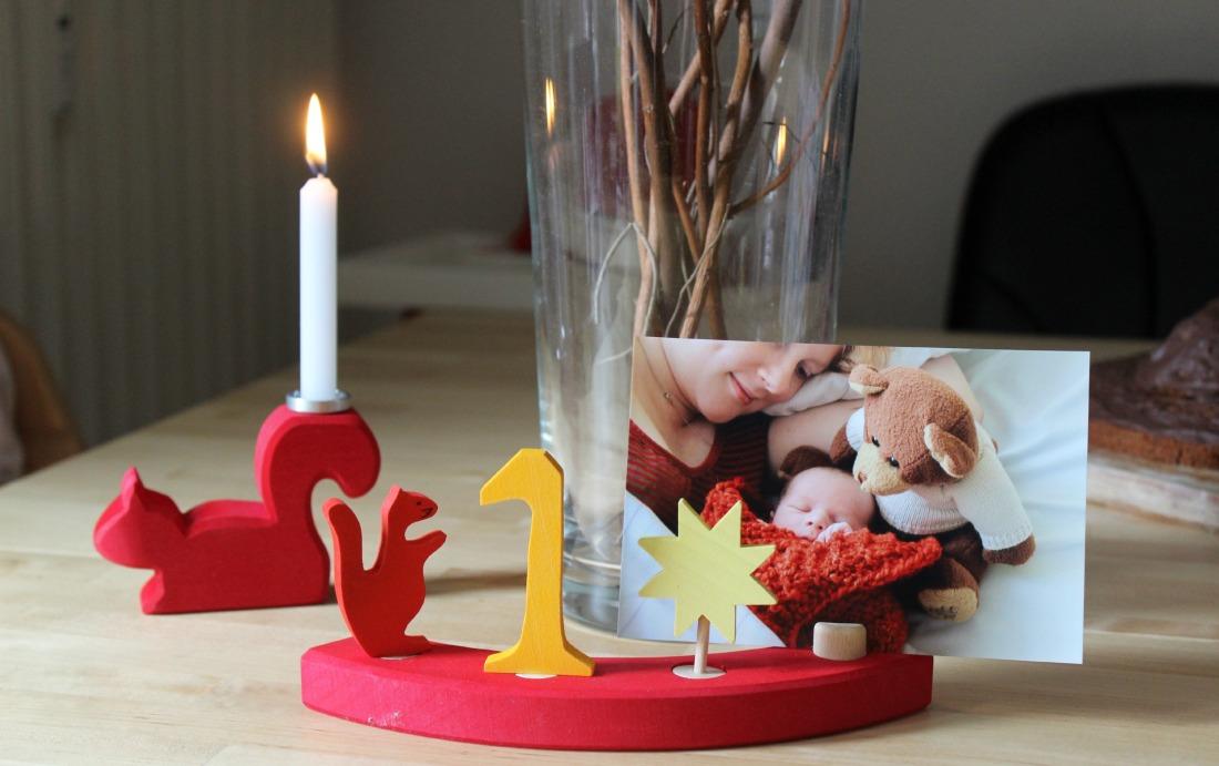 Ein Viertel aus einem Geburtstagsring aus Holz. in diesem Viertel stecken ein Holzeichhörnchen in rot, eine gelbe Holz-Eins, ein Holzstern mit 8 Zacken und ein Bilderhalter in dem ein Foto klemmt, auf dem ein Baby, so in eine Decke eingewickelt, dass nur das Köpfchen rausguckt, ein Bär und eine Frau zu sehen ist, die danebenliegt und lächelt. Der Ring steht auf einem Birkenholztisch, dhinter eine große Vaße mit trockenen Ästchen darin und daneben ein handbreites Holzeichhörnchen, auf dessen Schwanz eine brennende weiße Kerze sitzt.