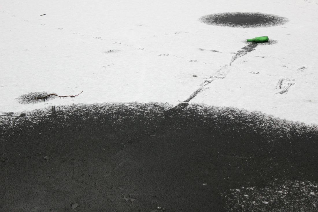 halb gefrorerener Weiher, mit angetauten Kreisen. Von einem dieser Kreise führt eine Tauspur zu einer leeren grünen Glasflasche auf dem eis.