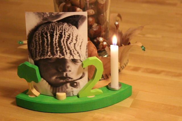 Vor einer mit Kastanien gefüllten Vase, die mit einer Krone aus getrockneten ahornblättern umfasst sind, an deren Spitzel grüne Pailletten und silberne Miniglöckchen kleben, steht ein grünes Viertel aus einem Holzgeburtstagsring, in dem eine brennende weiße Kerne, eine grüne 2, ein kleiner Baum und ein Schwarz-Weiß-foto mit einem Babay, das die Augen geschlossen und schwarze Lippen hat, stecken. Es trägt eine Wollmütze, halb über die Augen gezogen.