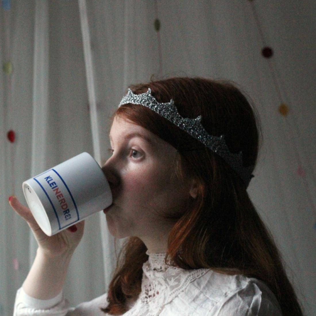 """Frau (ich) mit langen naturroten Haaren, einer kleinen silbernen Garnkrone um den Kopf und in einer Spietzenbluse. Im Hintergrund ein verschwommener Netzvorhang mit Pünktchen. Sie nippt an einer Kaffeetasse, auf der """"Kleinerdrei"""" steht, die Buchtstabenkombi """"Nerd"""" darin ist hervrogehoben. Sie guckt gelangweilt und spreizt den kleinen Finger ab."""
