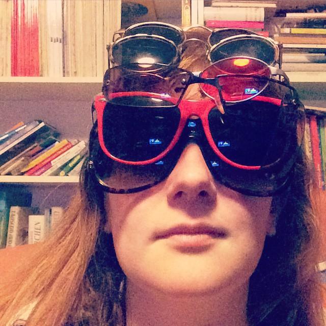 Selfie; ich trage sechs verschiedene Sonnenbrillen übereinander und gucke ins Lampenlicht.
