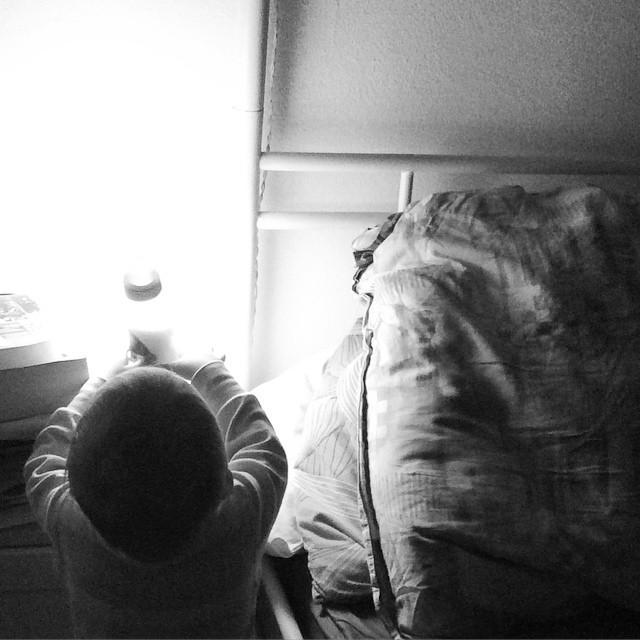 Das Kind steht neben dem Bett, von hinten fotografiert und hebt die Milchflasche mit beiden Arme hoch. Durch sie strahlt das Licht der Nachttischlampe.
