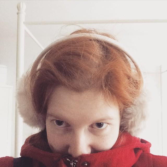 Selfie, in rotem Mantel und mit weißen Ohrenschützern auf dem Kopf, die Nase in den Mantelkragen gesteckt.