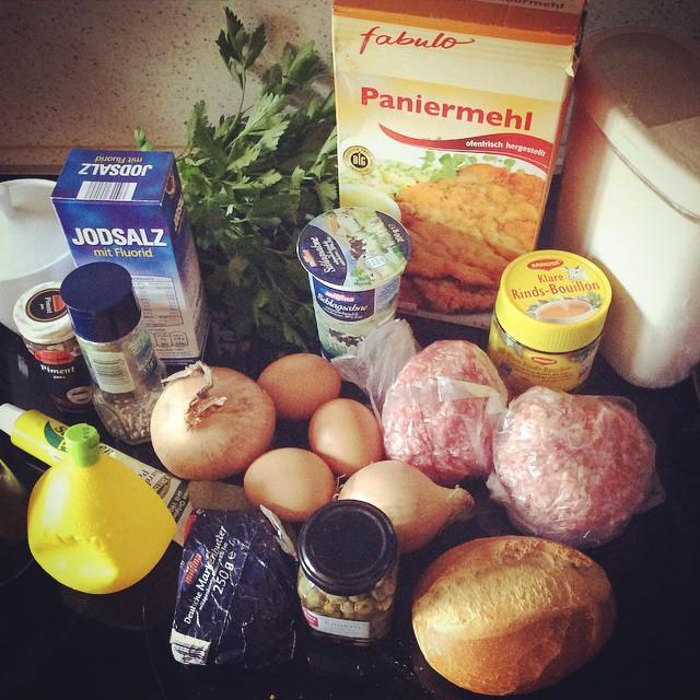 Paniermeh, Hackfleisch, Eier, Mehrl, Rinderbrühe, Brötchen, Kapern, Butter, Zitronensaft, Zwiebeln, Sahne, Salz, Petersilie, Piment, Sardellenpaste und mehr, auf dem Elektroherd dekorativ zusammengestellt.