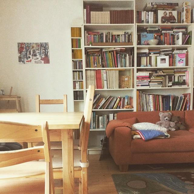 Ein Esstisch, ein Sofa, das vor weißen Billi-Bücherregalen voller Bücher steht, auf dem Sofa Decken und zwei Teddys, an der Wand ein Adventskalender.