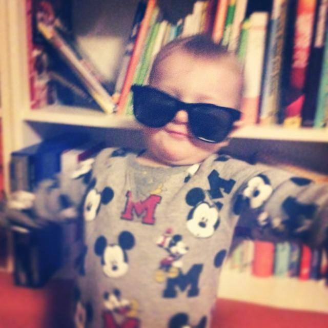 Kind in Sonnenbrille, die etwas von der Nase rutscht, es breitet seine Arme aus.