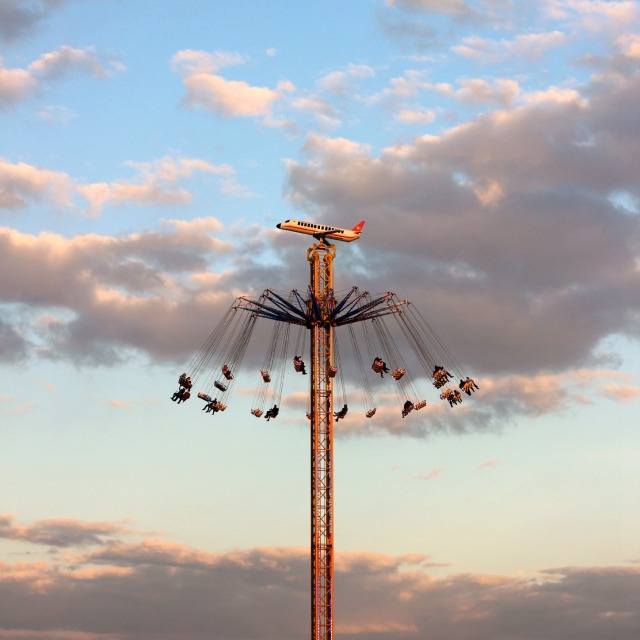 Kettenkarussel hoch in der Luft, an einem Turm. an dessen Spitze ein Flugzeug befestigt ist.