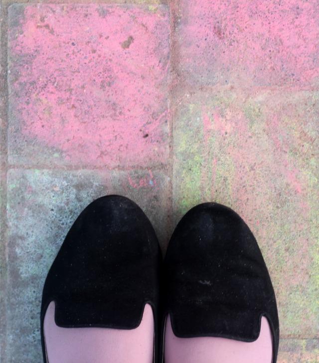Die Spitze meiner Schuhe auf mit pinker Kreide bemaltem Boden.